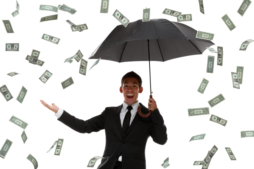 Excited businessman holding hand out in a money rain storm