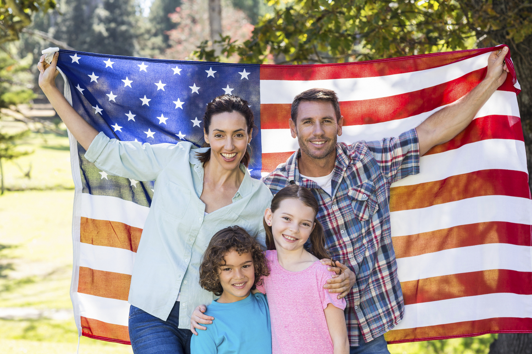 Happy family smiling with an american flag in a park on a sunny day